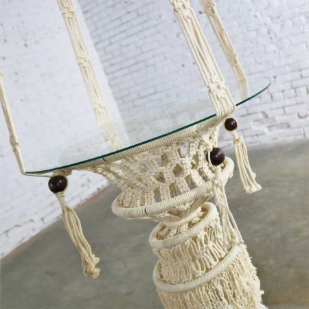 Beautiful pair of white cord macramé hanging tables with round glass tops. They are in wonderful age appropriate condition but not without minor flaws which do not take away from their overall look. Please examine photos. Circa 1960s-1970s.
